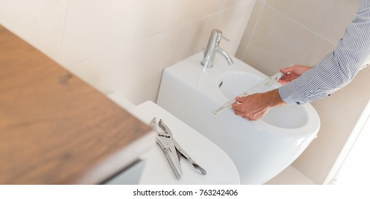 Architect taking measures of a brand new bathroom furniture. Home style and design concepts