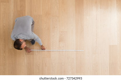 Architect taking measures of the new hardwood floor. Home and maintenance concepts
