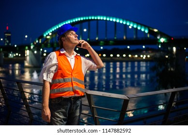 Architect talking on his mobile phone during blue hour by the river with illuminated bridge and city lights in the background