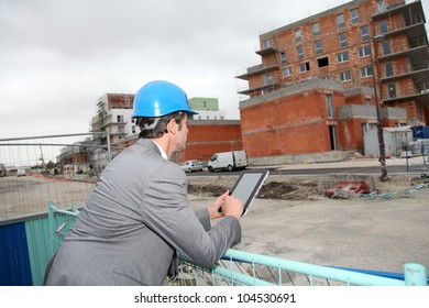 Architect using electronic tablet on building site
