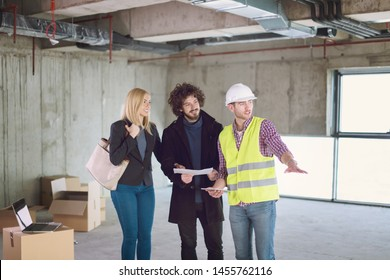 architect using tablet computer while showing house design plans to a young couple at construction site