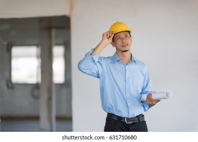 Architect wear yellow helmet is hold blueprint in his hand and looking outside.