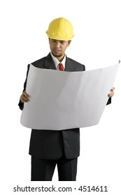 An architect wearing a hard hat and a suit looking at a blueprint