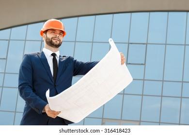 Architect wearing hardhat inspecting the blueprints outdoors