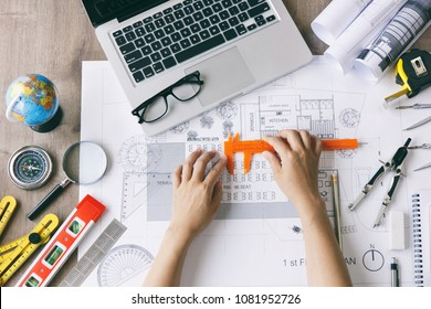Architect woman asian working on blueprint and equipments on desk at workplace