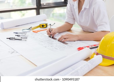 architect woman hands using laptop with a building of blueprint and engineering tools on working table.