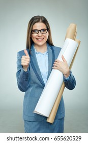 Architect woman wearing glasses holding blueprints shows thumb up. Isolated portrait of businesswoman.
