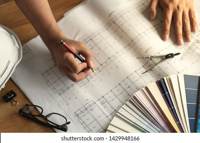 Architect working design blue print drawing on wood desk. ( Drawing document is made for stockphoto no copyright)