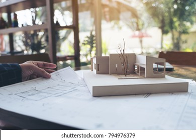 An architect working on an architecture model with shop drawing paper on table