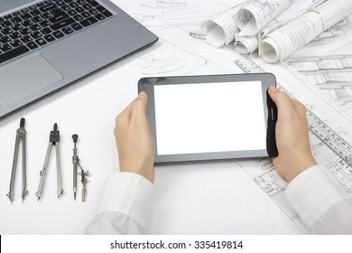 Architect working on blueprint. Architects workplace - architectural project, blueprints, ruler, tablet pc, laptop and divider compass. Construction concept. Engineering tools. Copy space for text.