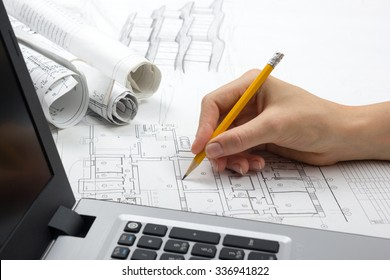 Architect working on blueprint. Architects workplace - architectural project, blueprints,  laptop. Construction concept. Engineering tools