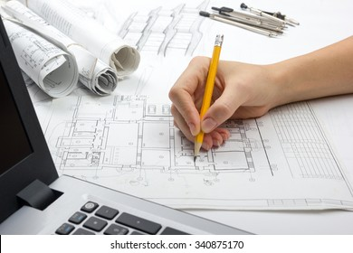 Architect working on blueprint. Architects workplace - Architectural project, blueprints, drawings, sketch, plan, laptop, pencil. Construction concept. Engineering tools