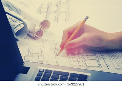 Architect working on blueprint. Architects workplace - architectural project, blueprints, ruler, calculator, laptop and divider compass. Construction concept. Engineering tools