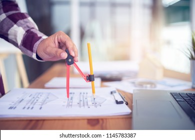 Architect working on blueprint with Circus.engineer inspective in workplace - architectural project, blueprints,ruler,calculator,laptop and divider compass. Construction concept. Engineering tools.