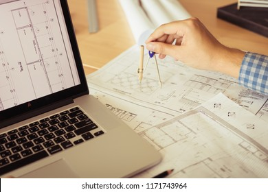 Architect working on blueprint in workplace with laptop and drawing compass.