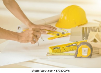 Architect working on blueprint.Architects workplace - architectural project, blueprints, ruler, calculator, laptop and divider compass.Construction concept.Engineering tools. engineering students.