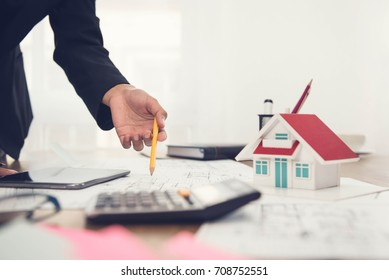 Architect working on house model and design layout for a proposal