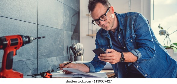 Architect working on a kitchen project and using smart phone