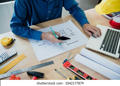 Architect working on new project blueprint with ruler,calculator,laptop and divider compass. Construction and architect concept.Close up