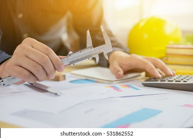 architect working,Businessman with new startup project in modern loft. Drawning pen,inspection engineer report with product and vernier calipers,engineering architectural project concept