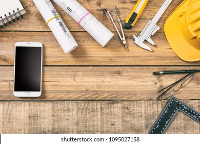 Architect workplace, construction site desk. Smartphone with black blank screen, project blueprints and engineering tools on wooden table, copy space, top view