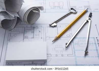 Architect worplace top view. Architectural project, blueprints, blueprint rolls and  divider compass, key, blank business card on plans. Construction background. Engineering tools. Copy space