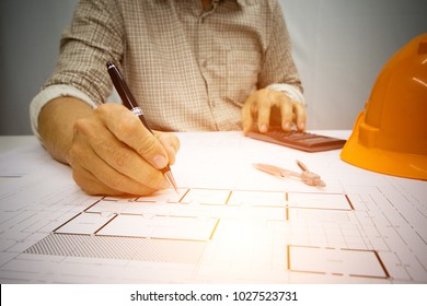 Architect Writing home project  on the desk with a blueprint in the office, Vintage, Sunset light.Selective Focus at Construction Site