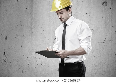 Architect writing on a clipboard on construction site