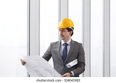 Architector in hardhat and business suit with construction plans