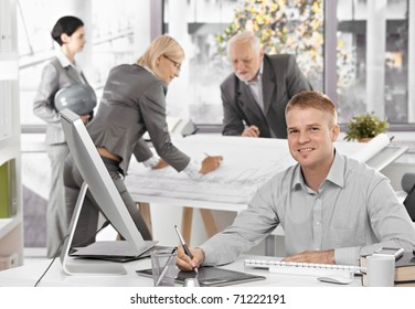 Architects busy at work, young designer in focus sitting at desk using drawing pad, smiling at camera.?