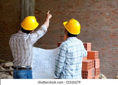Architects at a construction site looking at blueprints and pointing