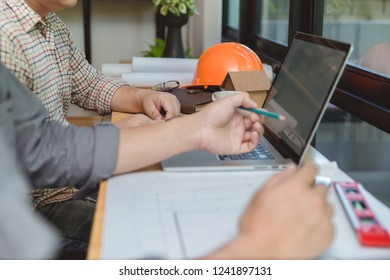 Architects engineer discussing on desk with laptop and blueprint. Team group on construciton site check documents and business workflow.Construction concept. Engineering tools.Selective focus.
