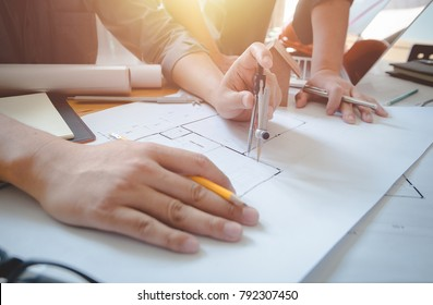 Architects engineer discussing on desk with blueprint. Team group on construciton site check documents and business workflow.Construction concept. Engineering tools.Vintage effect.Selective focus.
