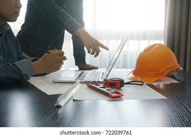 architects and engineer discussing on working table with blueprint and construction tools - business and industrial concept