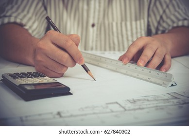 Architects engineer drawing plan at the table with blueprint - Closeup on hands and project print, construction site check documents and business work-flow. Successful male architect. Vintage style.