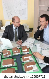 Architects gathered around a desk exchanging ideas