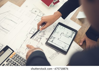 Architects or interior designers discussing floor plan blueprints on the table
