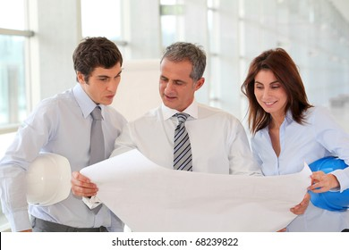 Architects meeting in hall with construction plan
