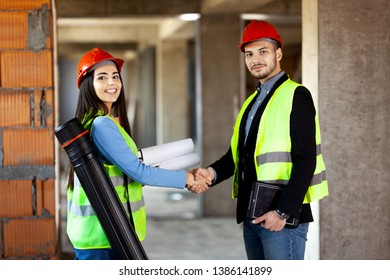 architects shaking hands. construction site engineers on site making a deal. satisfied expressions