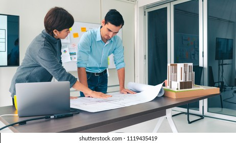 Architects team are working on a blueprint of building floor plan. Woman suggest requirement to designer. concept of construction, architecture, development and creative.