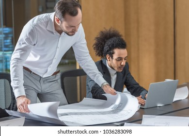 architects working with building plans together at office