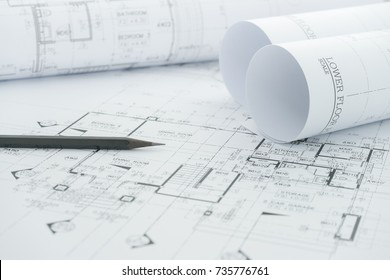 architects workplace - architectural blueprints with measuring tape and black pencil on table.