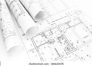 Architect's workspace with rolled building plans and blueprints