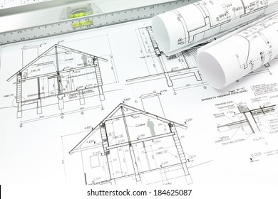 Architect's workspace with rolled house plans and blueprints
