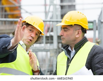 Architects with yellow safety jacket and helmet at work. Outdoors