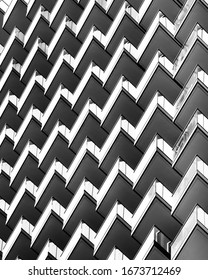 Architectural background, black and white. Detail of balconies in modern apartment building. Zigzag pattern, abstract composition.