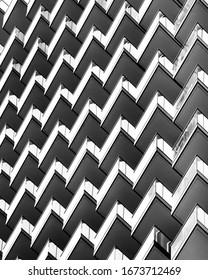 Architektur, schwarz-weiß. Detail der Balkone in modernen Appartementhaus. Zigzag-Muster, abstrakte Komposition.