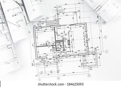 Architectural background with floor plans and rolled technical drawings