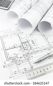 Architectural background with floor plans, rolls of technical drawings and work tools