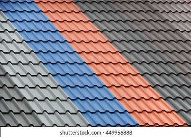 Architectural background. Texture of a metal roof tiles of black, gray, blue and red colors.